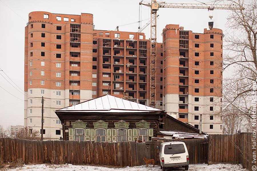 Деревянный дом на фоне многоэтажки