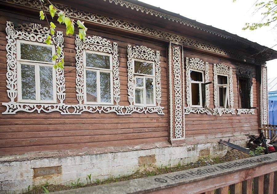 Погоревший дом с изображением сов на резных наличниках