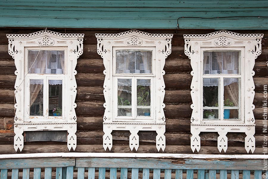 Три белых наличника на бревенчатом доме
