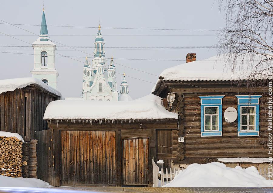 Деревянная изба и купол церкви на заднем плане