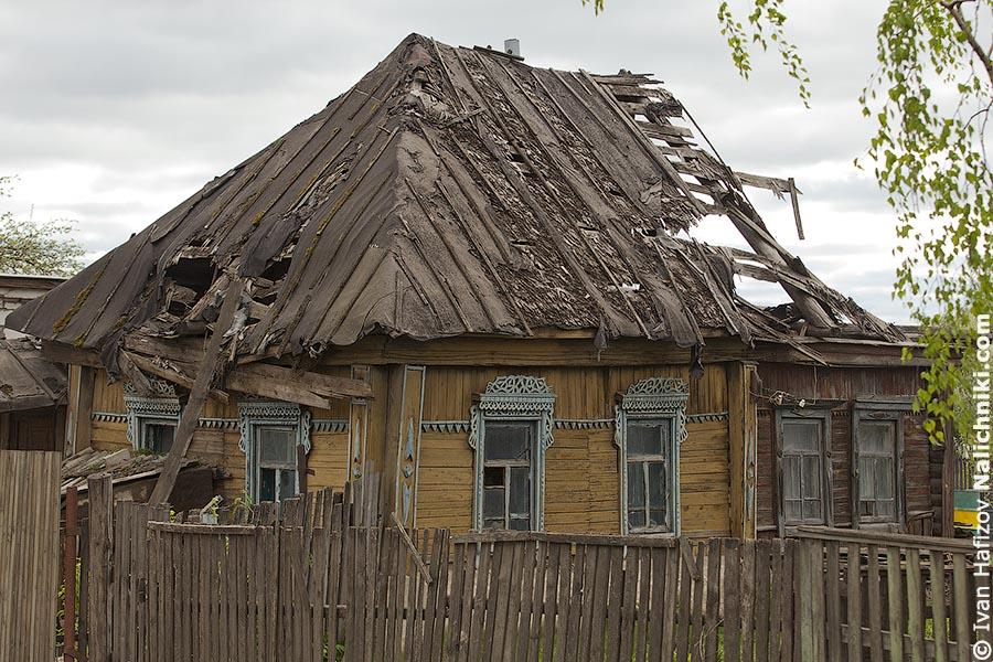 Деревянный дом с резными наличниками и двускатной крышей