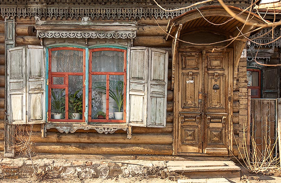 Ornate window frame and a porch on russian izba