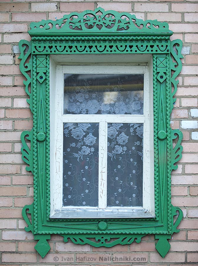 Wooden carved window frames on a brick house