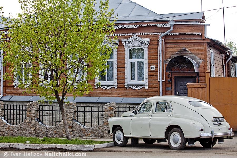 Деревянный дом с наличниками и машиной