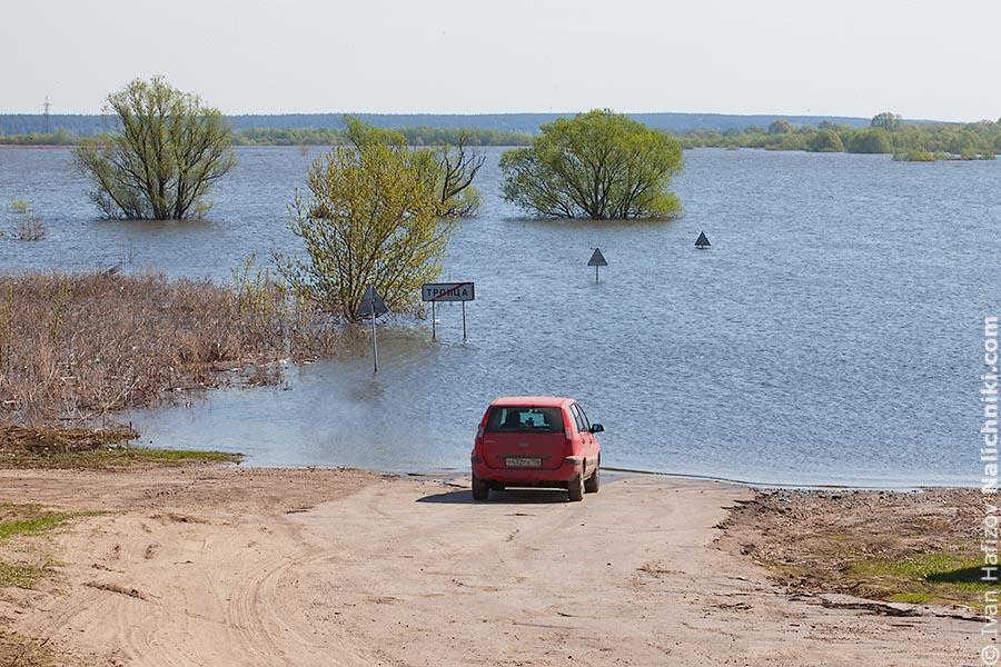 красная машина перед затопленной дорогой весной