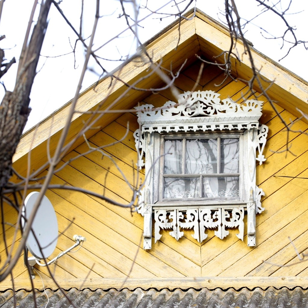 An attic window at one of wooden Russian houses in Lyubim city