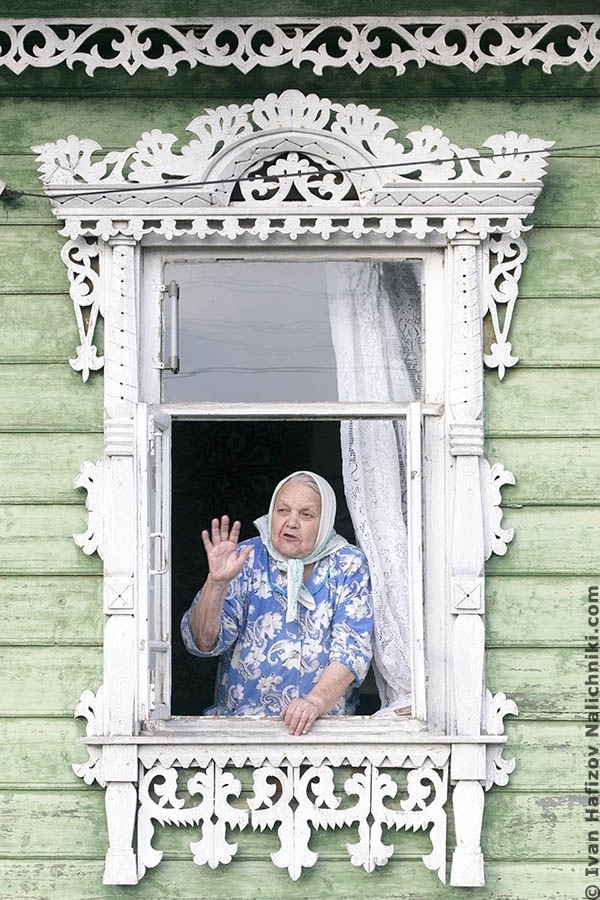 Granny in a kerchief in window with beautiful nalichnik