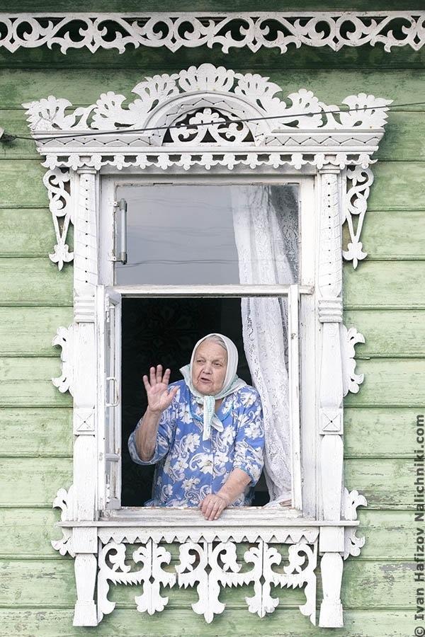 бабушка в платочке смотрит из окна с наличником
