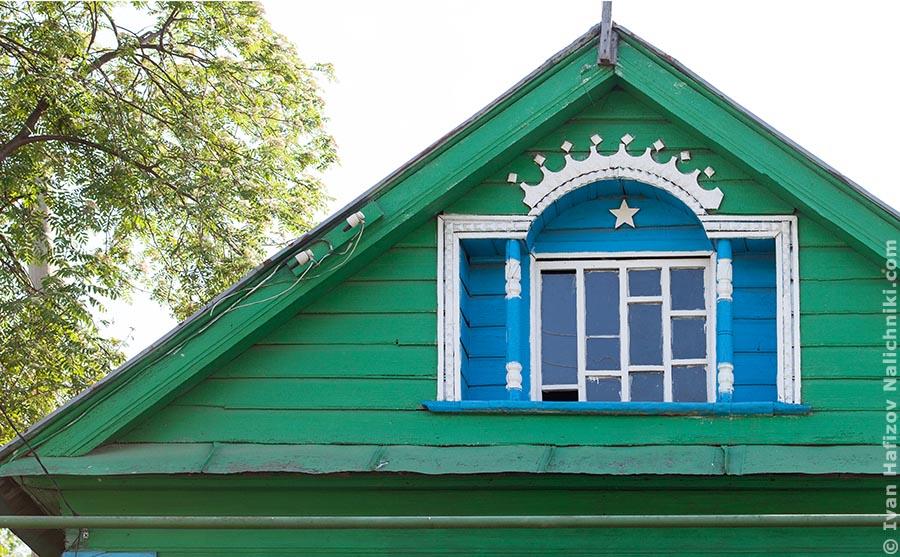 A dormer window with nalichniki on a wooden house pediment in Kazan city