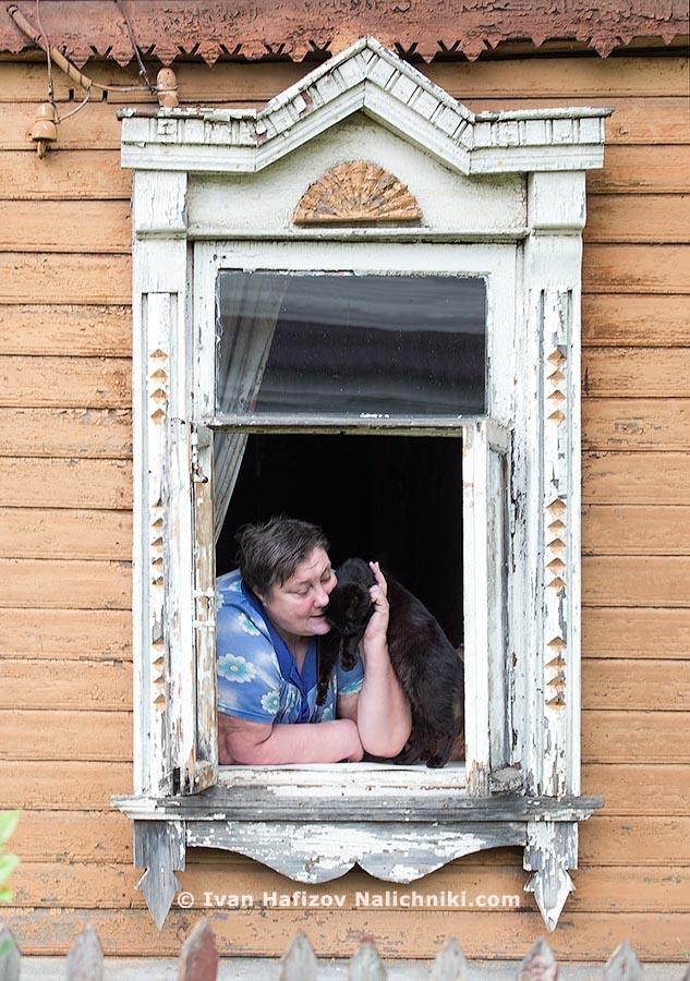 Традиционный русский наличник и женщина с котом в окошке