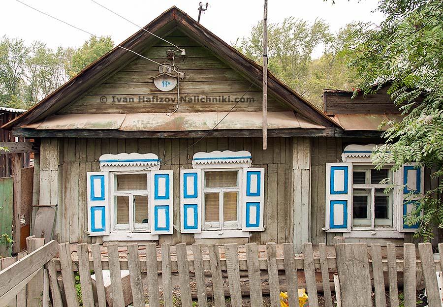 Резной деревянный дом с наличниками и сугрбовами на них