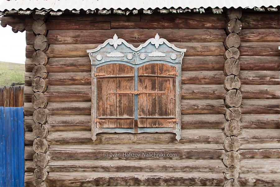 Стена старого дома с закрытыми ставнями