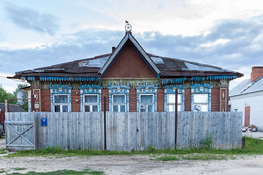 деревянный дом с резными наличниками, скрытый за забором
