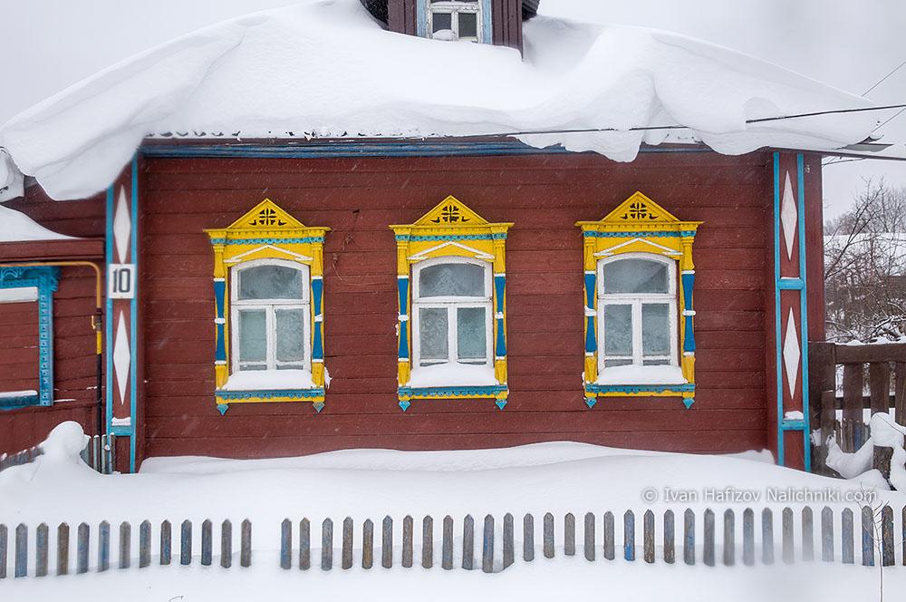 Оконные наличники на деревянном доме в  снегу